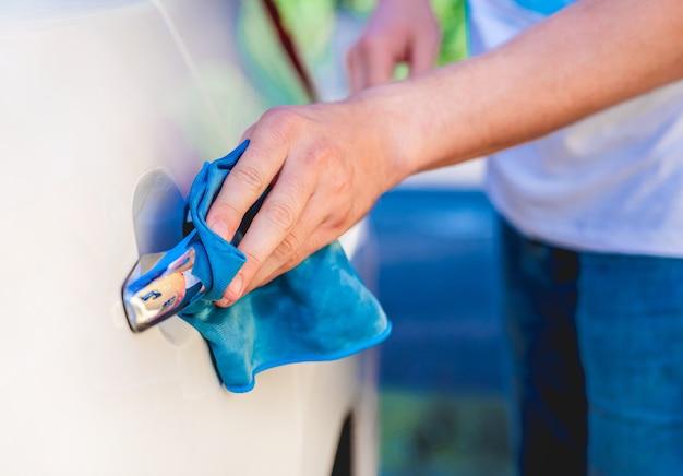 Hand with microfiber rag polishing car handle