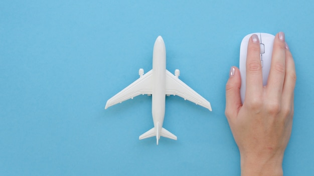 Hand with mouse beside airplane toy