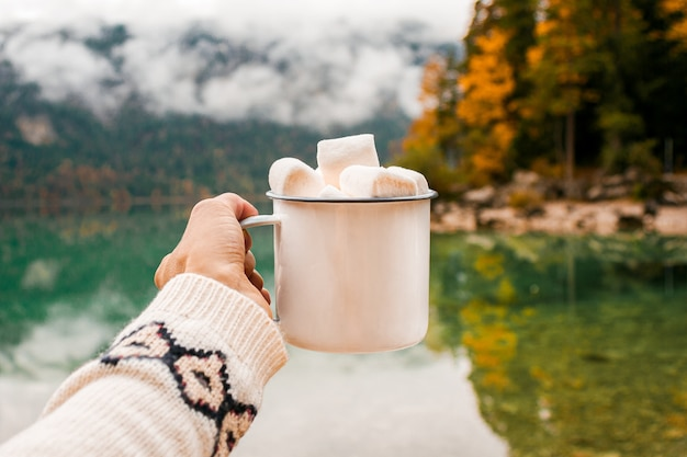 Hand with mug of cacao, marshmallow on the lake background in bavarian alps, germany