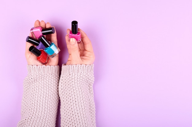 Hand with nail polish bottles.