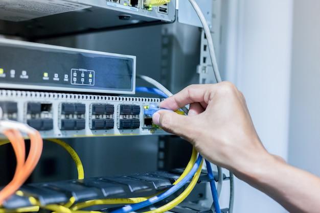 Рука с сетевыми кабелями, подключенными к серверам в центре обработки данных