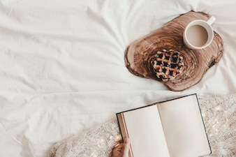 Hand with notebook near biscuit and hot drink on stand on bedsheet