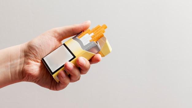 タバコのパックを持つ手