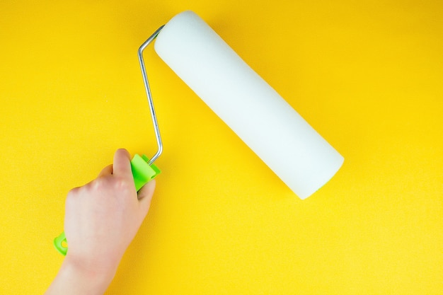 Hand with paint roller on yellow background.