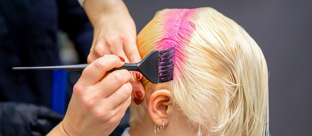 헤어 살롱에서 핑크 색상의 여자의 흰 머리카락을 염색하는 붓으로 손