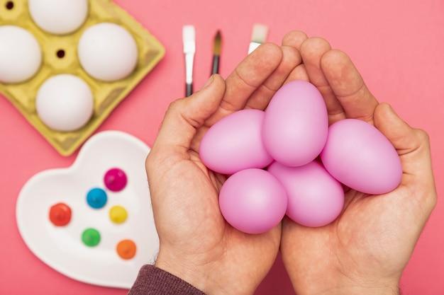 Рука с крашеными яйцами