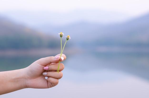 湖の背景と花のコートボタンを保持している塗られた爪を持つ手