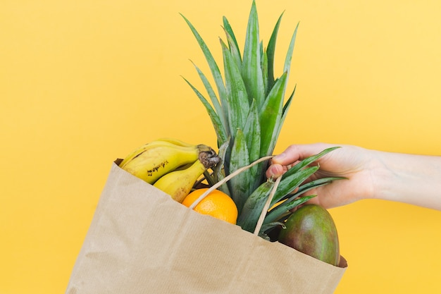 Hand with paper bag with assorted fruit on yellow background.
