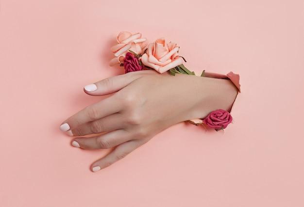 종이 꽃과 페인트 손톱으로 손을 종이의 구멍을 통해 밀어 넣습니다.