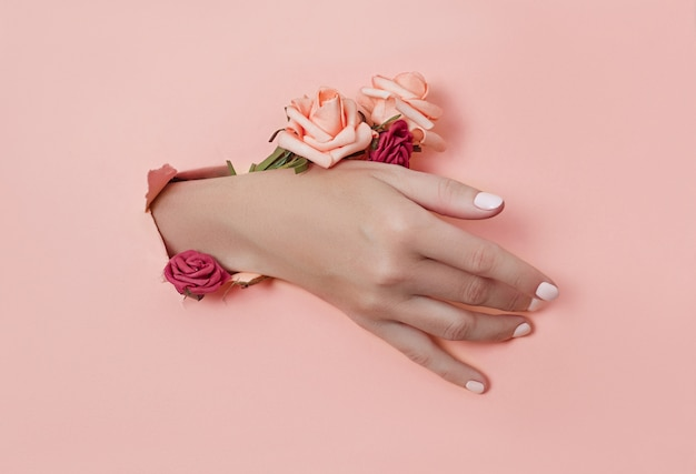 Hand with paper flowers and painted nails is thrust through a hole in the paper background