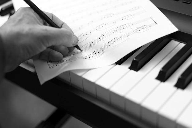 펜과 음악 시트 손-음악적 배경
