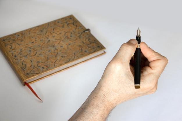 중립 흰색 배경에 펜과 메모장으로 손.