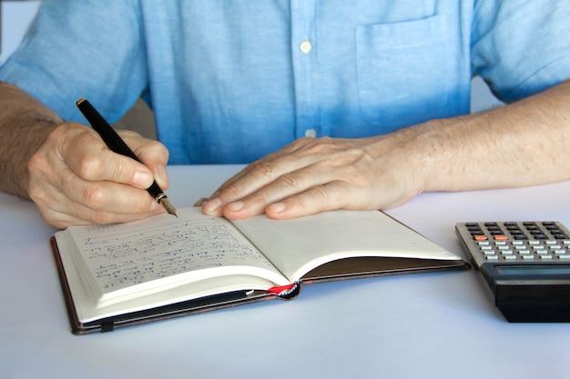 계산기 옆에 작성 된 펜과 메모장으로 손.