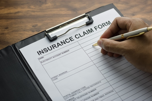 Hand with pen on application form fot registering claim health insurance