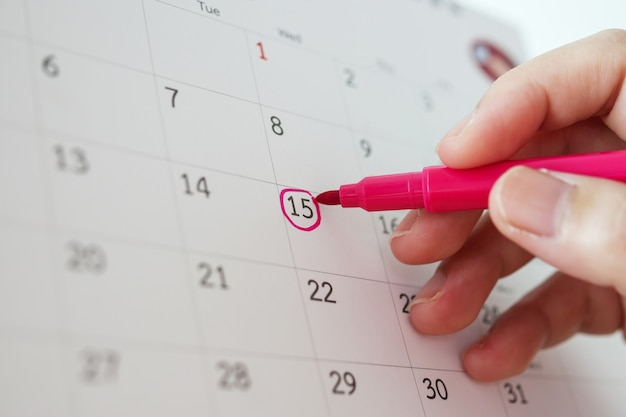 Hand with pen mark at 15th on calendar date