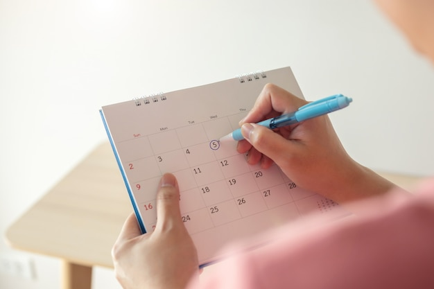 Hand with pen mark at 5th on calendar date with blue circle