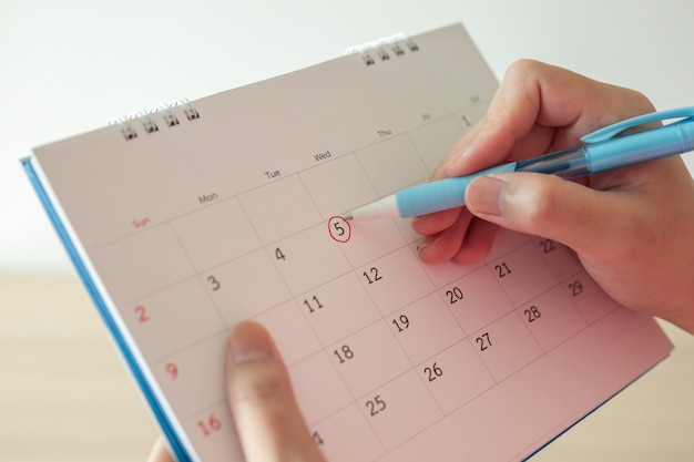 Hand with pen mark at 5th on calendar date with red circle