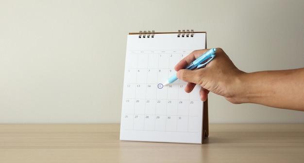 Рука с отметкой пера на 15-й календарной дате