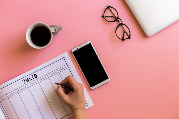 Hand with pen near calendar, smartphone, cup of drink and eyeglasses