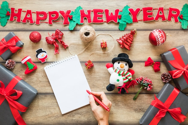 Hand with pen near notebook, present boxes and happy new year inscription