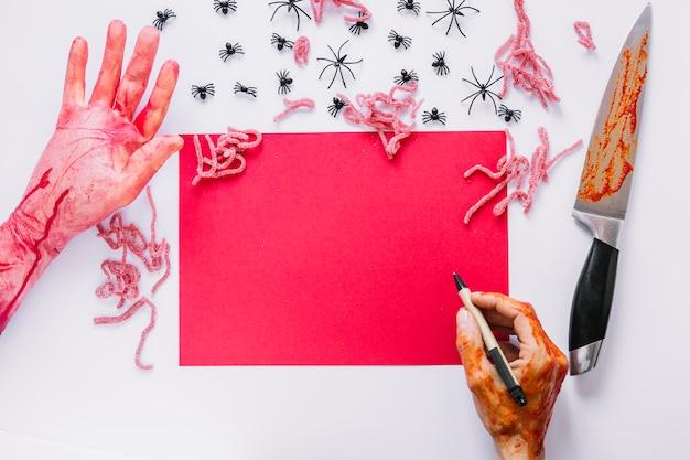 ハロウィーンの装飾に囲まれた紙の近くにペンで手