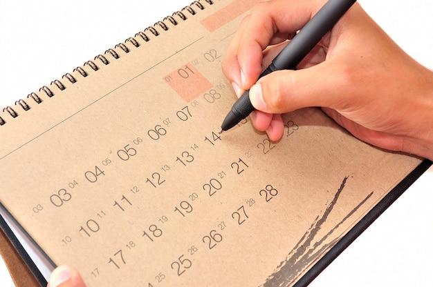 ペンで手はカレンダーにメモを取ります