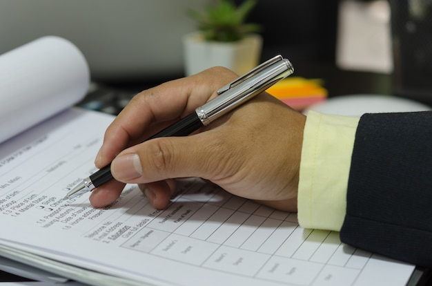 Hand with pen write application documents on desk.