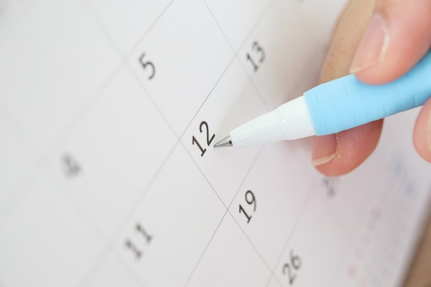 Hand with pen writing on calendar date