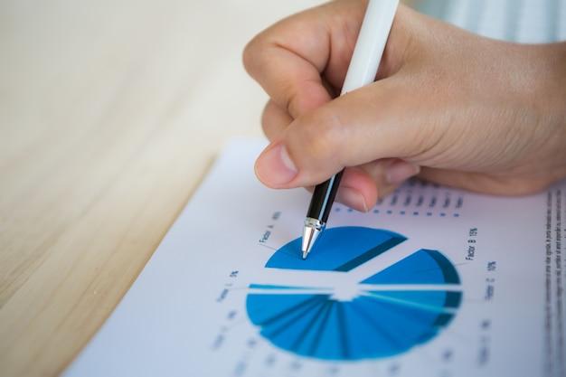 Mano con una penna che scrive su un documento con un grafico a torta
