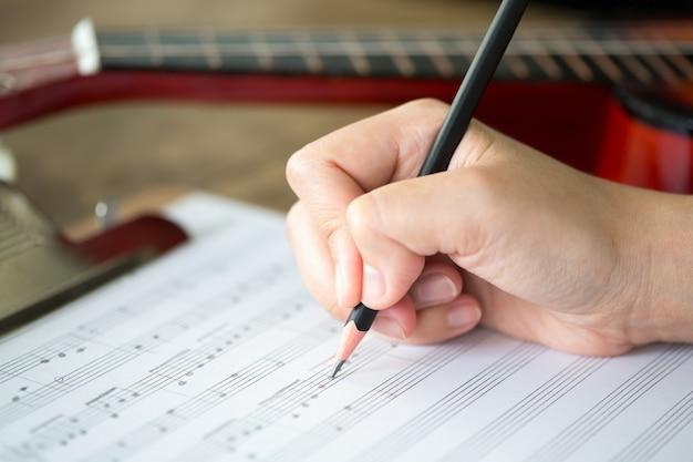 연필과 음악 시트와 손