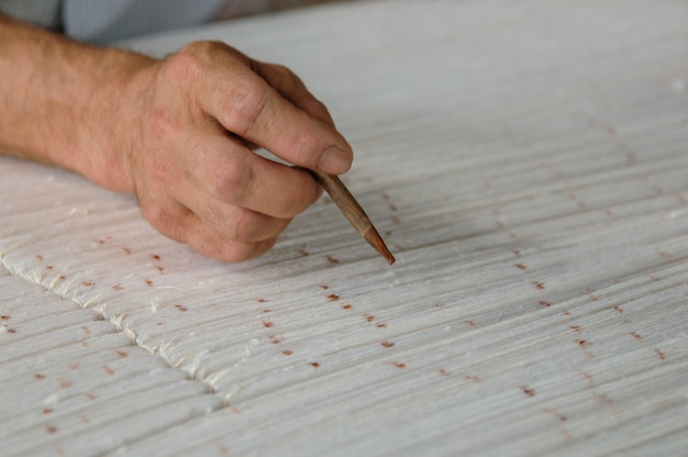Hand with a pencil makes marks on the carpet weaving and manufacturing of handmade carpets closeup