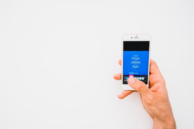 Mano con il telefono premendo come pulsante in facebook con spazio di copia