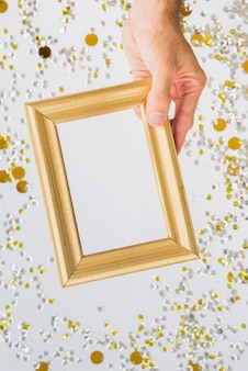 Hand with photo frame between colourful confetti