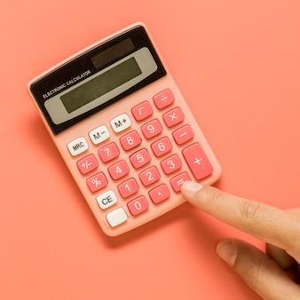 Рука с розовым калькулятором на цветной поверхности