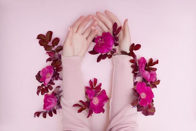 Рука с розовыми цветами и лепестками, лежащими на бумажном фоне. косметика для ухода за кожей рук. натуральная косметика с лепестками, эфирные масла, уход за руками против морщин и старения