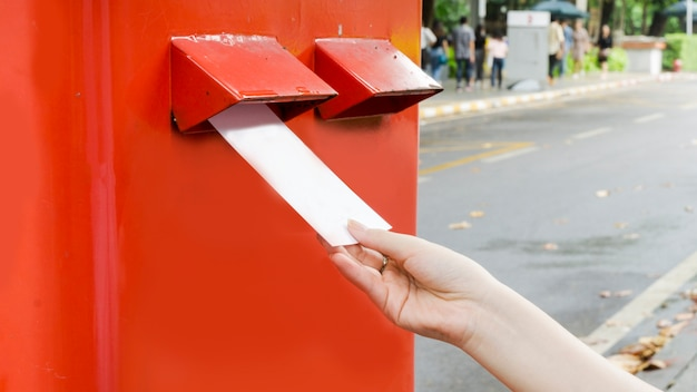 Hand with postcard and drop in red mail postbox