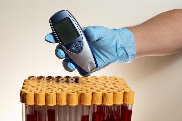 Рука с защитной нитриловой перчаткой держит глюкометр с пробирками для забора крови.