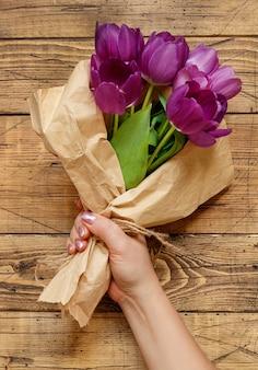 나무 테이블에 공예 종이에 보라색 튤립 꽃다발 손 클로즈업