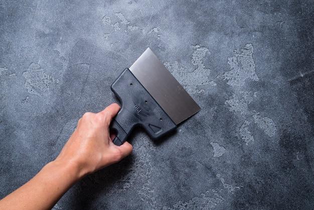 灰色の背景にパテナイフを持つ手