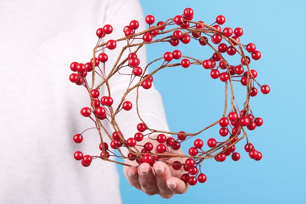 赤い果実の花輪、分離されたクリスマスの装飾を持つ手