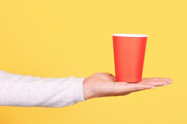 Рука с красной одноразовой чашкой изолирована