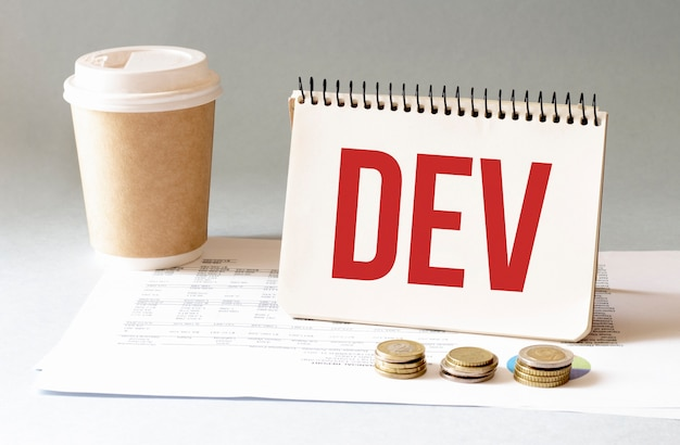 Hand with red pen, cofee cup, stick and dev sign in the notepad