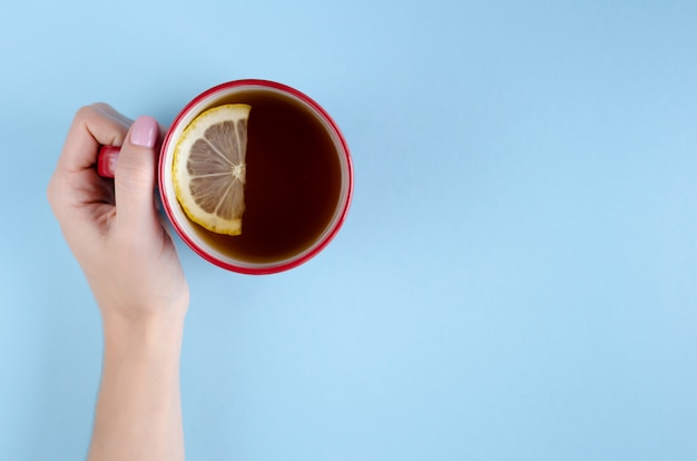 Hand with red tea cup and lemon slice composition on blue background.