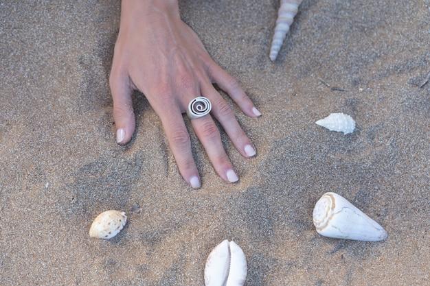 Рука с кольцом на песке на пляже с ракушками вокруг