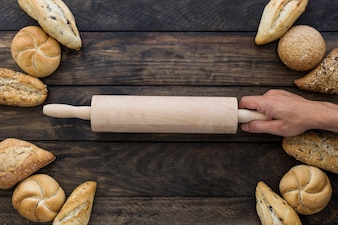 Hand with rolling pin on desktop with bakery