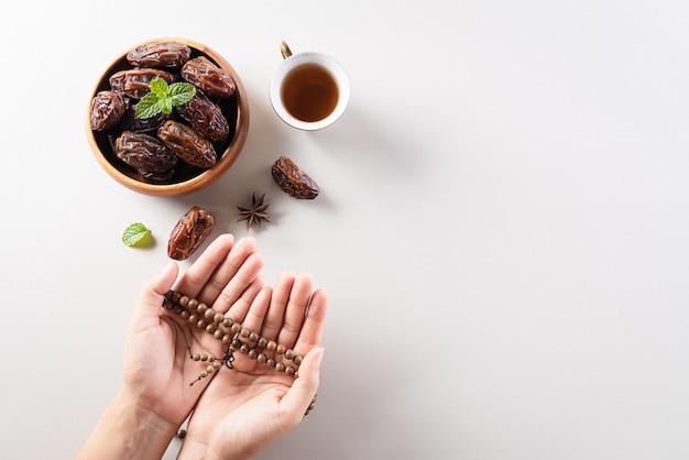 ラマダンの壁のロザリオと日付のフルーツを持つ手