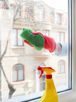 Hand with rubber glove cleaning the window