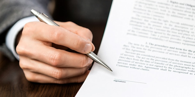 The hand with the silver ballpoint pen points to an empty space for the signature.
