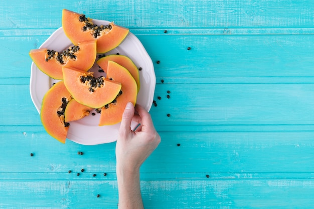 Hand with slice of papaya on blue background . plate with pieces of papaya. copy space. top view.