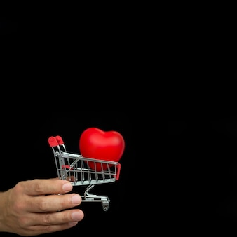 Hand with small shopping trolley and red heart on dark background